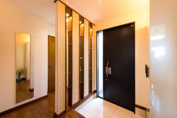玄関の間仕切り壁には、圧迫感を感じさせないガラスの棚を設置。照明を点けるとガラスに反射し、より一層明るい玄関に。